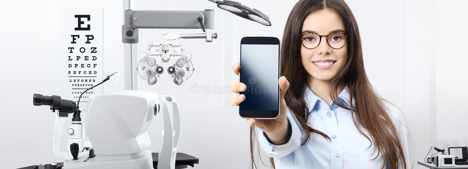 Concept of eye examination, smiling woman with spectacles showing mobile phone in optometrist office, contact us, appointment and stock photos
