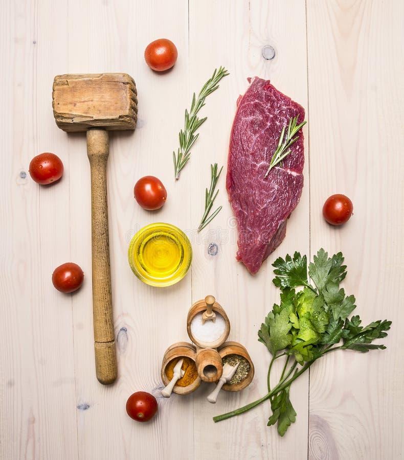 Concept faisant cuire le bifteck de boeuf cru, le romarin, le marteau en bois pour battre la viande, le pétrole, les herbes et le images libres de droits