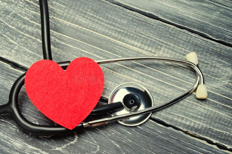 The concept of family medicine and insurance. stethoscope and heart on a wooden background royalty free stock photography