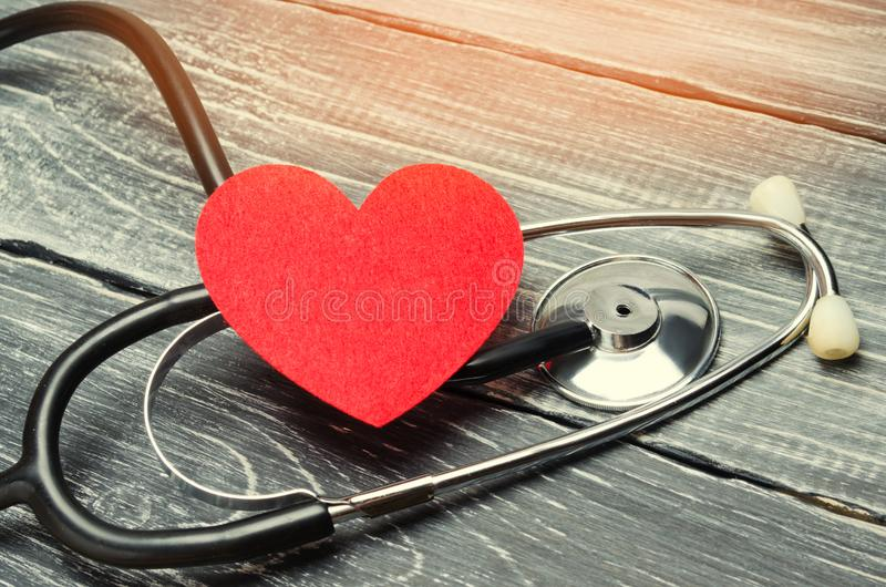 The concept of family medicine and insurance. stethoscope and heart on a wooden background stock image