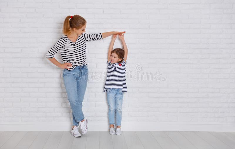 concept of the family. mother measures growth of child to daughter near empty wall royalty free stock photography