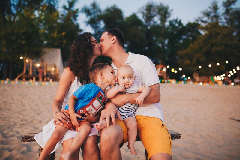The concept of a family vacation. Young family sitting on a bench in the evening on a sandy beach. Mom and Dad kiss, the older bro stock photos