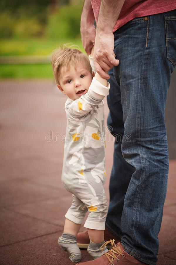 Adorable baby hold hands and try to stand with help of his father. Concept: family values. Portrait of adorable innocent funny brown-eyed baby hold hands and try stock images