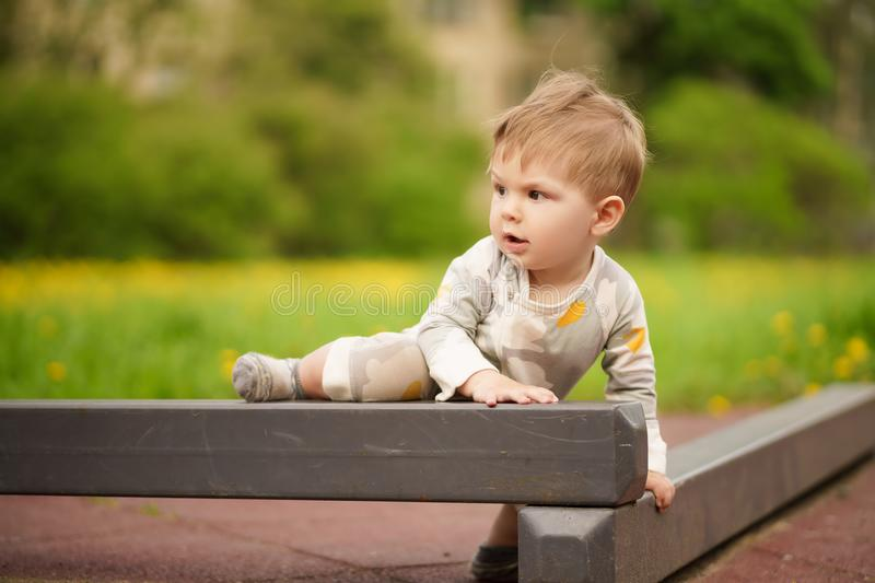 Adorable baby play at outdoor playground with serious face. Concept: family values. Portrait of adorable innocent funny brown-eyed baby play at outdoor stock images