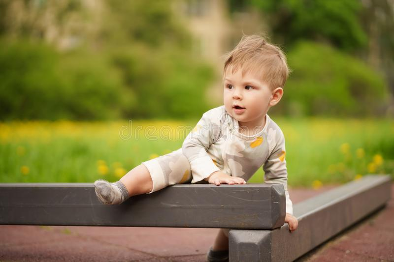 Adorable baby play at outdoor playground with serious face. Concept: family values. Portrait of adorable innocent funny brown-eyed baby play at outdoor stock photography