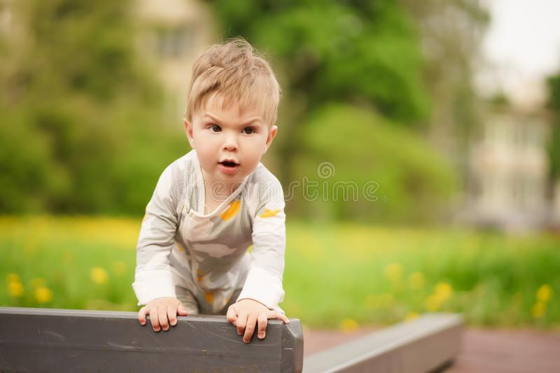Adorable baby play at outdoor playground with serious face. Concept: family values. Portrait of adorable innocent funny brown-eyed baby play at outdoor stock image