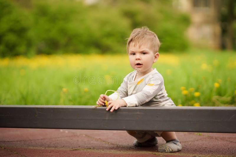 Portrait of adorable baby playing at playground. Concept: family values. Portrait of adorable innocent funny brown-eyed baby playing at outdoor playground stock photos