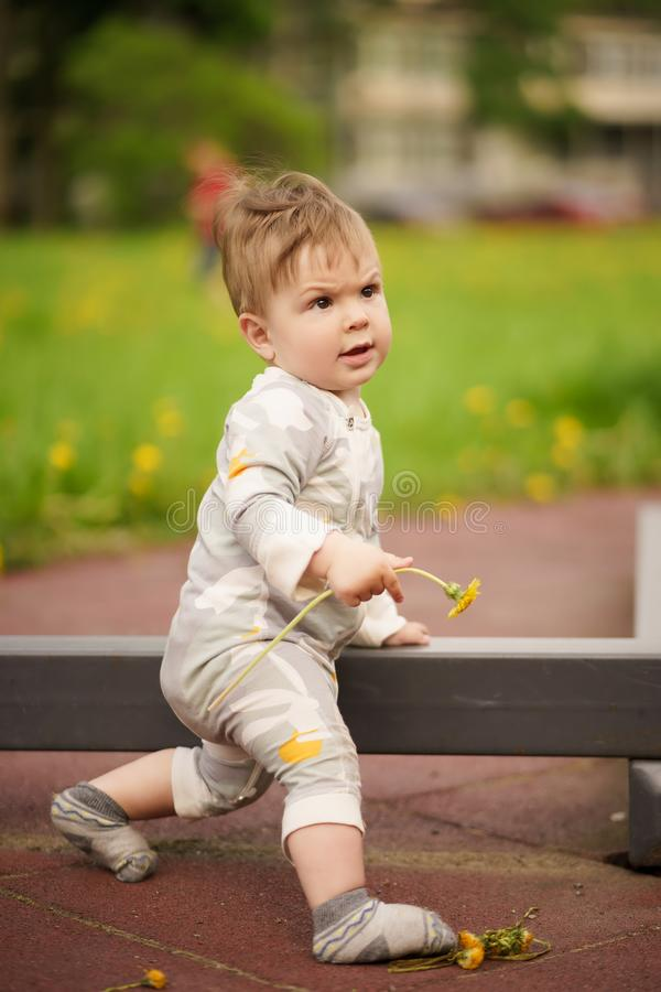 Adorable baby play at outdoor playground with serious face. Concept: family values. Portrait of adorable innocent funny brown-eyed baby playing at outdoor royalty free stock image