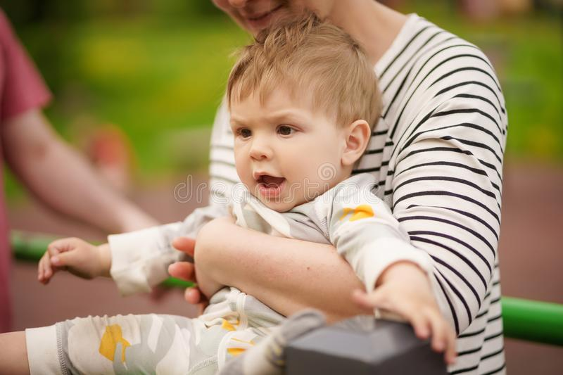 Portrait of adorable baby smiling and playing with his mother. Concept: family values. Portrait of adorable innocent funny brown-eyed baby smiling and playing stock photography