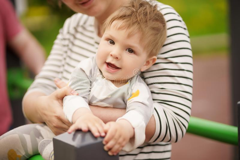 Portrait of adorable baby smiling and playing with his mother. Concept: family values. Portrait of adorable innocent funny brown-eyed baby smiling and playing royalty free stock photos