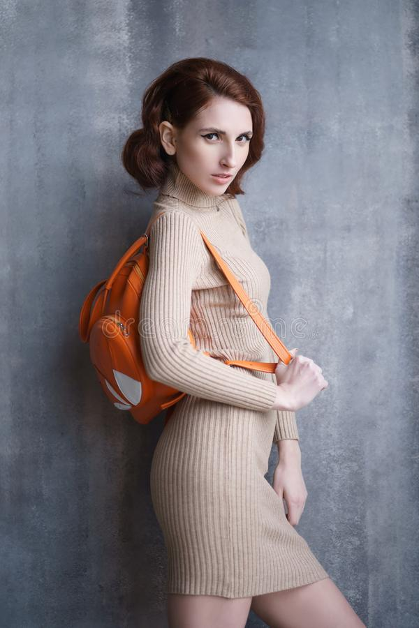 Pretty redhead thin lean young woman with vintage hairdo posing in knit dress. Studio photoshoot royalty free stock photo