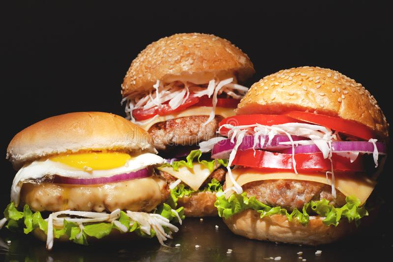 Concept: fast food big burgers on a black table. Large double cheeseburger with cutlets and fresh vegetables on a dark background. royalty free stock photo