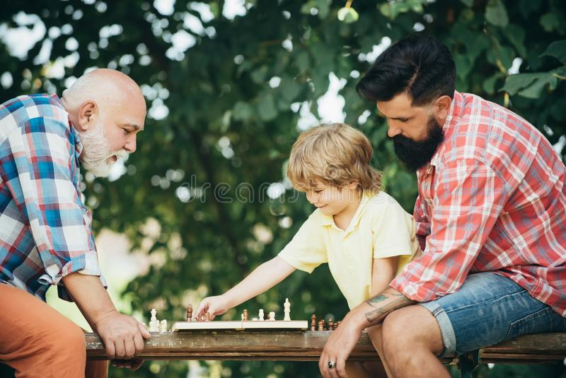 Concept of Fathers day. Senior man teaching his grandson to play chess. Happy man family concept playing Chess and have stock image