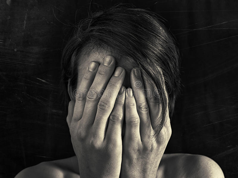Concept of fear, domestic violence. Woman covers her face her hands. Dim light and black, scratched background creates a dramatic mood of this black and white royalty free stock photography