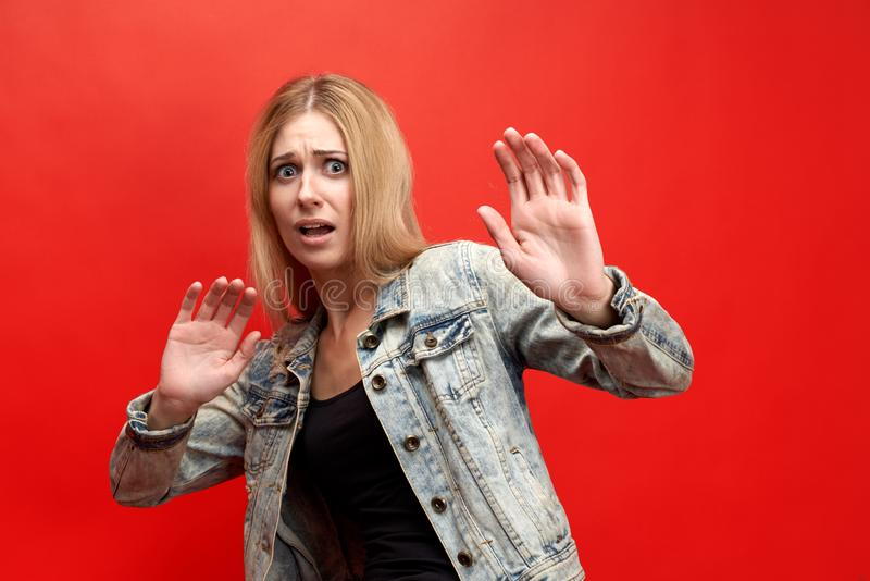 The concept of fear, horror, fright. The modern young lady in fear tries to fence off her hands, with a frightened face royalty free stock photography