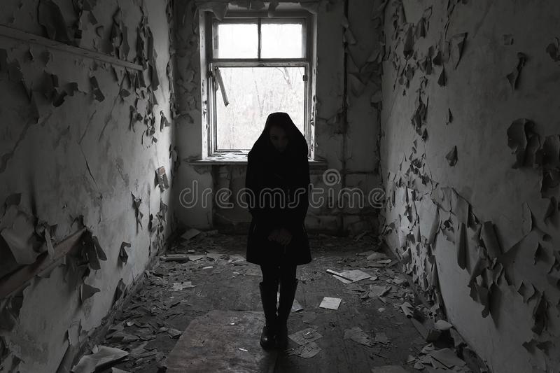 The concept of fear of loneliness. One girl stands in a dark room with old walls by the window. Black and white photo royalty free stock images