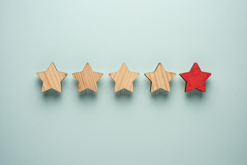 The concept of feedback of five stars. One red star in addition to the four ordinary ones. stock image