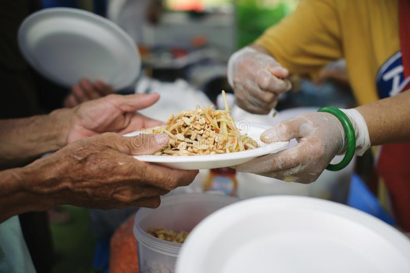 The Concept of Feeding : The poor have been sharing food from the kinder society to Relieve Hunger : Social concept of poor people. Sharing : Concept serving stock photography