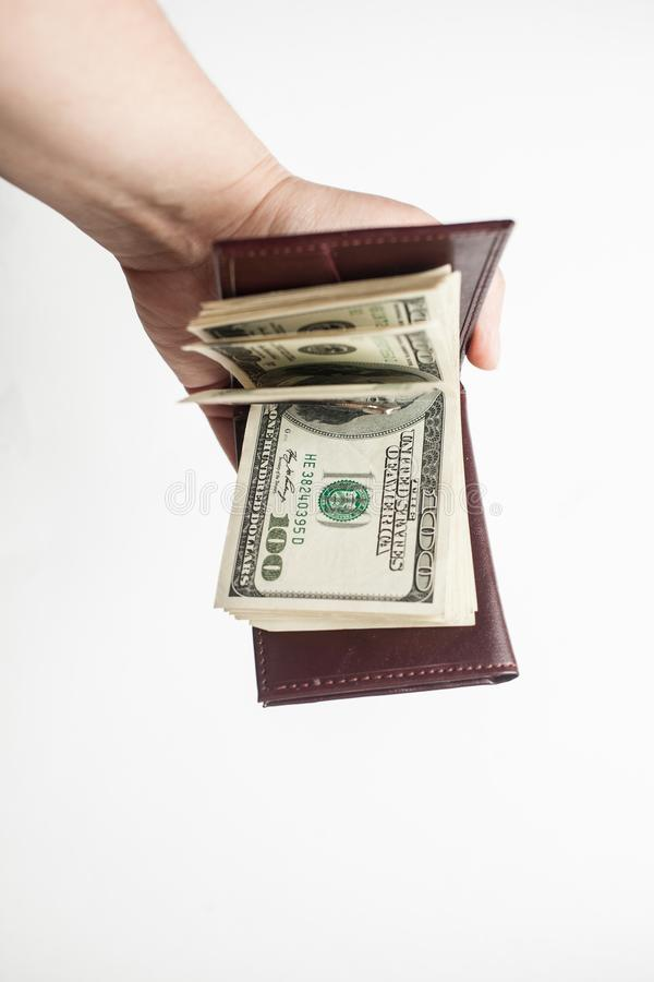 Female hand holds opened brown wallet with a thick wad of one hundred dollar bills. isolated over a white background royalty free stock photos