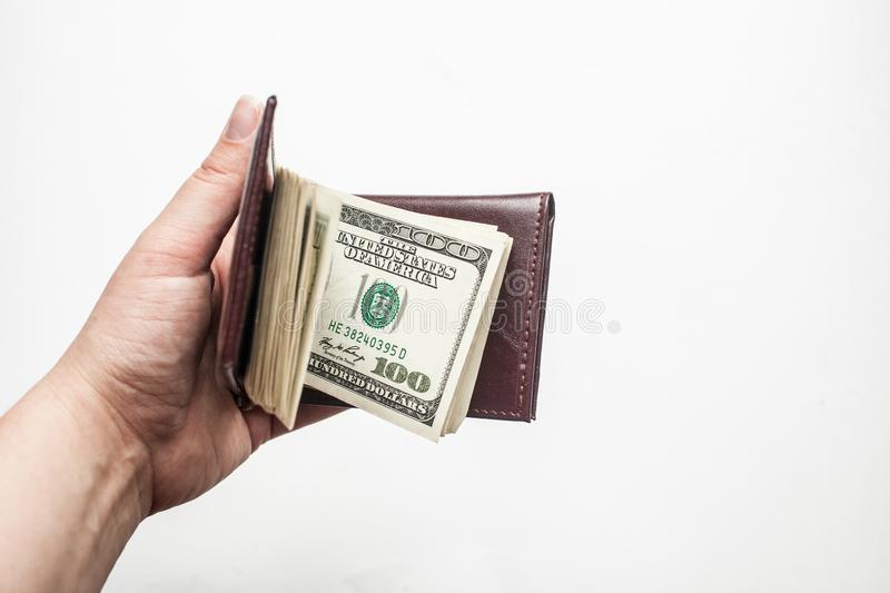 Women hand holding a wallet full of one hundred dollar bills isolated over a white background royalty free stock images