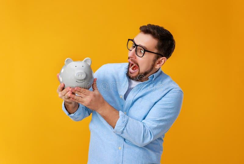 Concept financi?n en zaken mens met spaarvarken op gele kleur als achtergrond stock afbeeldingen