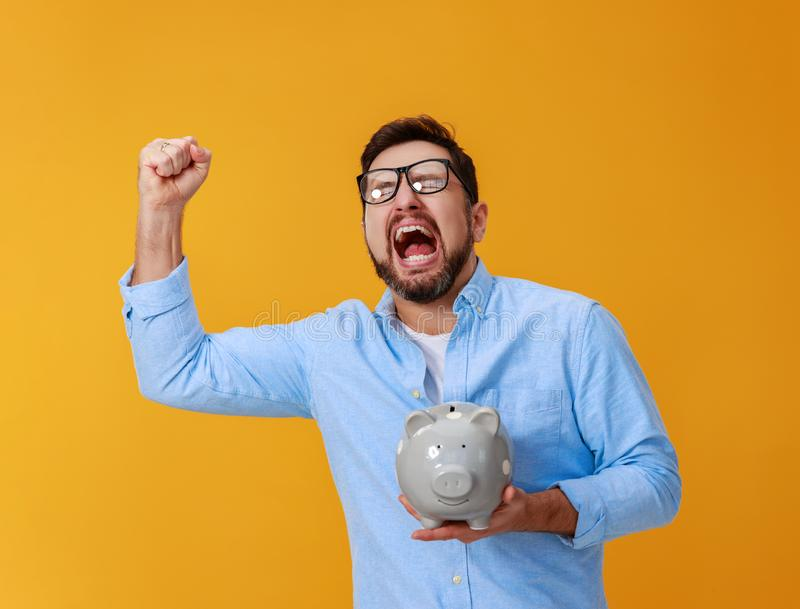 Concept financi?n en zaken mens met spaarvarken op gele kleur als achtergrond royalty-vrije stock afbeelding