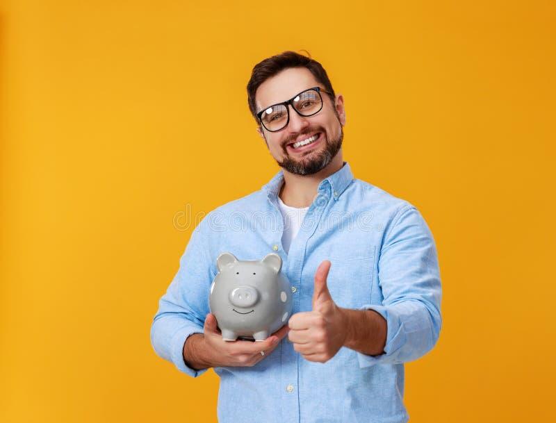 Concept financi?n en zaken mens met spaarvarken op gele kleur als achtergrond stock afbeelding