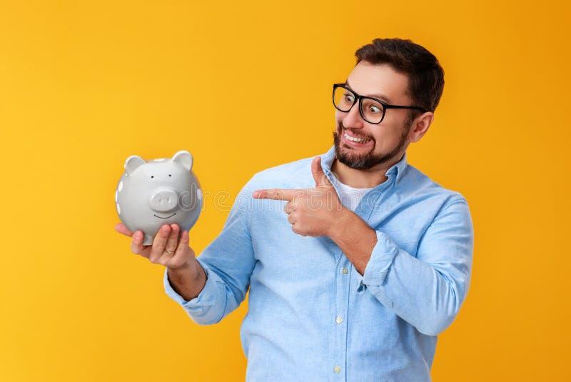 Concept financi?n en zaken mens met spaarvarken op gele kleur als achtergrond royalty-vrije stock fotografie