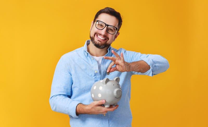 Concept financi?n en zaken mens met spaarvarken op gele kleur als achtergrond royalty-vrije stock foto