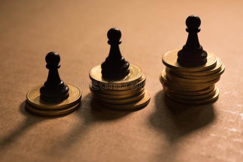 Concept of financial business competition. Chess pawn on coins stack royalty free stock image