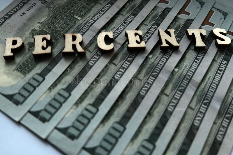 The word PERCENTS is lined with wooden letters on the background of hundred-dollar bills. The concept of financial transactions an stock images