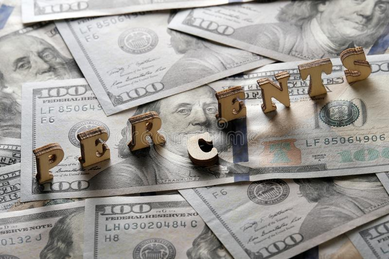 The word PERCENTS is lined with wooden letters on the background of hundred-dollar bills. The concept of financial transactions an royalty free stock photos