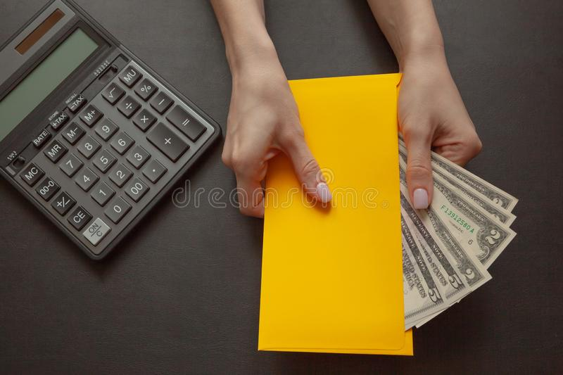 The concept of financial well-being, the girl in her hand holds a yellow envelope with money stock photo