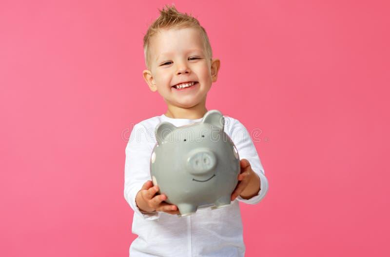 Concept financier de l'argent de poche des enfants garçon d'enfant avec la tirelire sur un fond rose coloré image stock