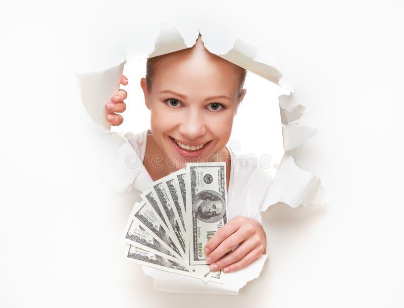 Concept financier, femme heureuse avec l'argent dans le dollorov de mains jetant un coup d'oeil par un trou dans un livre blanc v photo libre de droits