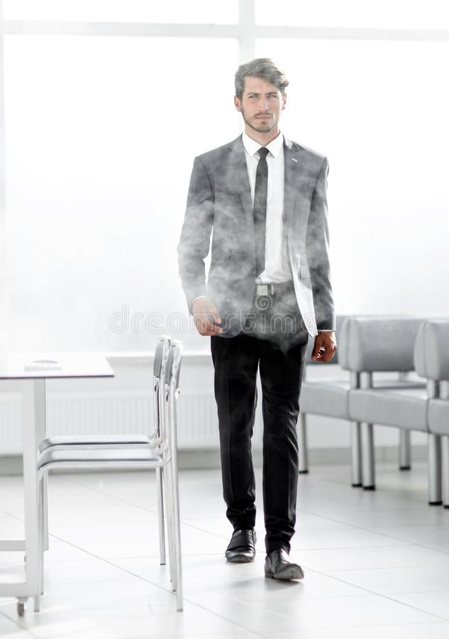 Full-length businessman in a smoky office. The concept of fire alarm. Businessman in full growth in a smoky office stock image