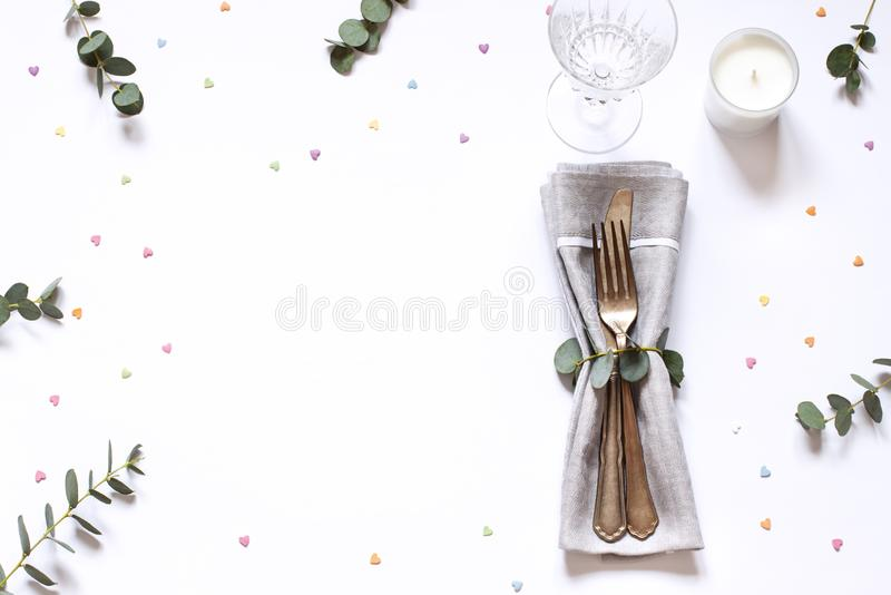 Concept flat lay with floral decorations and cutlery on the white backdround. Top view Valentines day, Mothers day or Easter card royalty free stock image