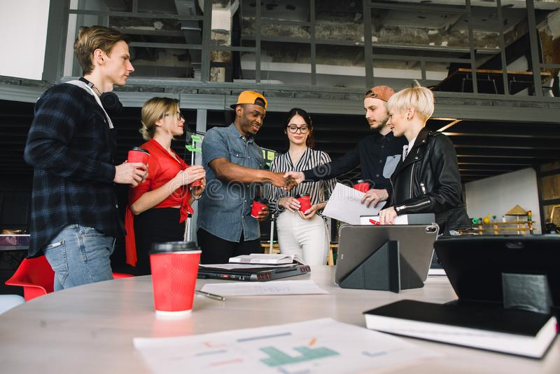 Concept fonctionnant contemporain de connexion de local commercial Groupe de six collègues en café potable de tenue de détente et image stock