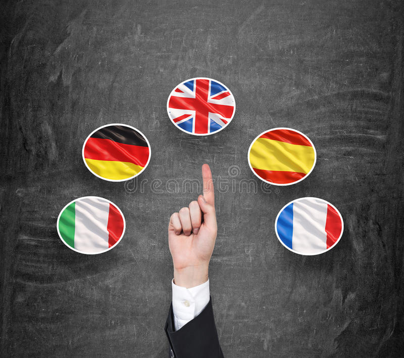 A concept of foreign language studying process. A finger is pointing out the Unites Kingdom flag as a priority in choice of. Foreign languages. Black chalkboard royalty free stock photo
