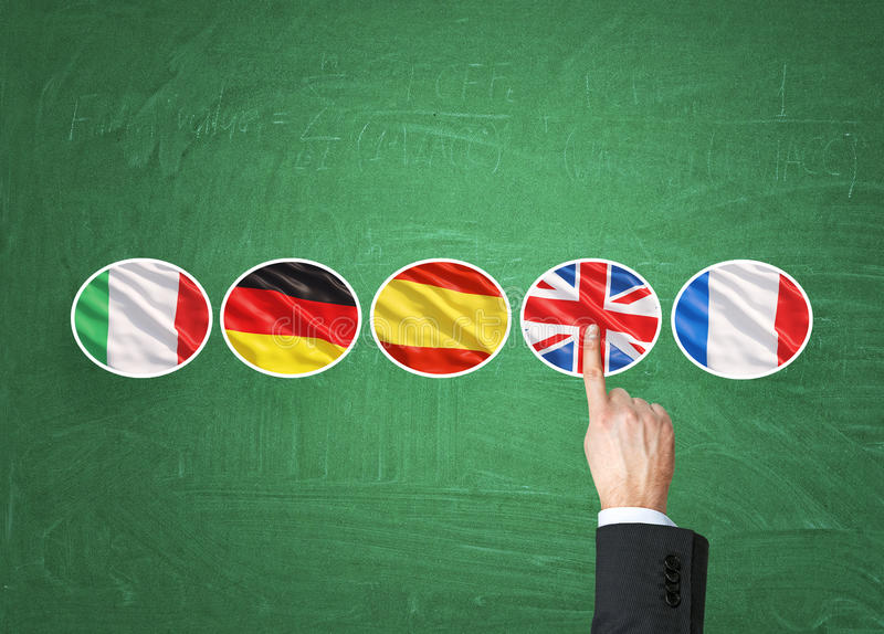 A concept of foreign language studying process. A finger is pointing out the Unites Kingdom flag as a priority in choice of. Foreign languages. Green chalkboard stock photo