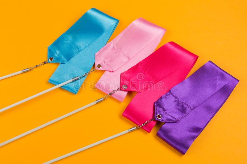 Concept, four colored gymnastic ribbons close-up on a yellow background. Side view royalty free stock photos