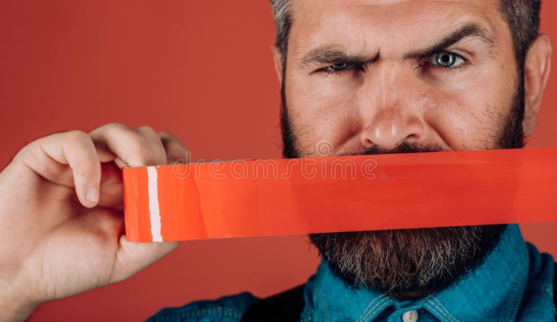 Concept freedom of speech and press. censorship. Brutal bearded male. Mind control and propaganda. International Human. Right day. man wrapping mouth by royalty free stock photography