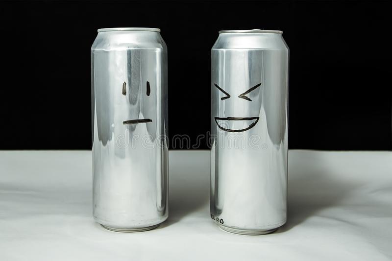 Concept of friends. Joke over a friend but it`s not funny. Aluminium cans with drowing emoticons, Emoji of laugh and poker face.  royalty free stock photography
