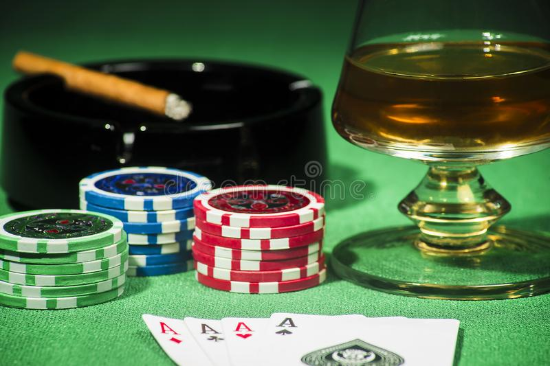 The concept of gambling, cards and chips with a glass of cognac and a cigar royalty free stock photo