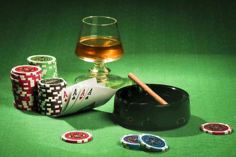 The concept of gambling, cards and chips with a glass of cognac and a cigar royalty free stock photos