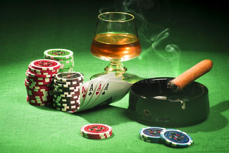 The concept of gambling, cards and chips with a glass of cognac and a cigar royalty free stock image