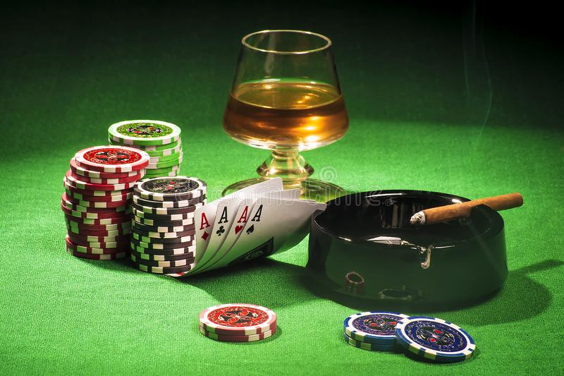 The concept of gambling, cards and chips with a glass of cognac and a cigar royalty free stock images
