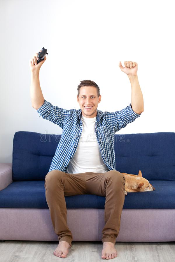 The concept of the game. the guy is playing a video game with a joystick at home with a dog. A smiling man in a shirt, sitting on. The couch, plays a video game royalty free stock photography