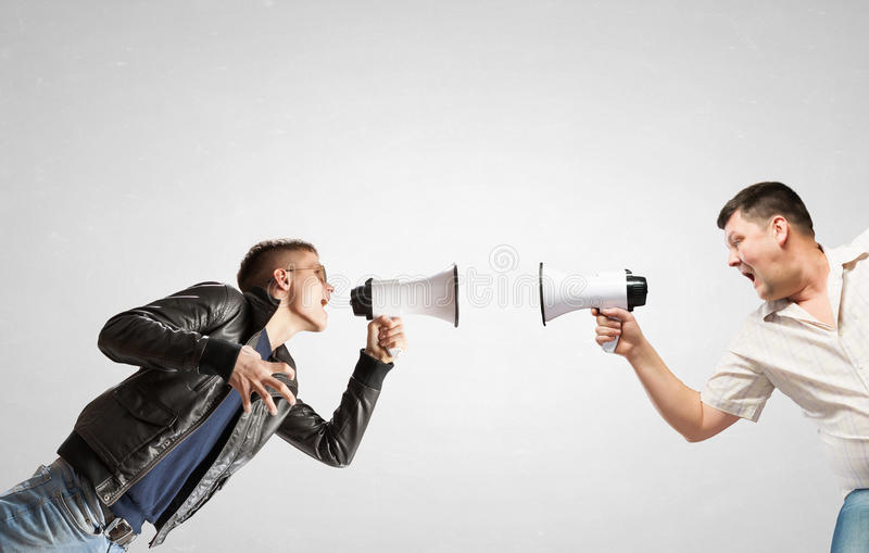 Concept of generation conflict. Young men in casual screaming emotionally in megaphone stock photo