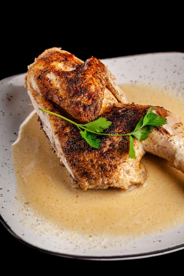 The concept of Georgian cuisine. Half a baked chicken in garlic sauce with crispy crust on a white plate, on a black background royalty free stock photography